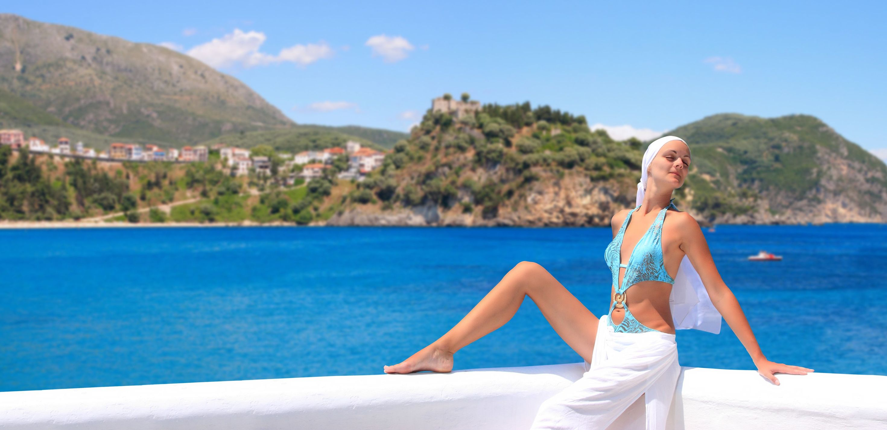 Visit-Greece-Beautiful-Young-Woman-Relaxing-by-The-Beach-in-Greece