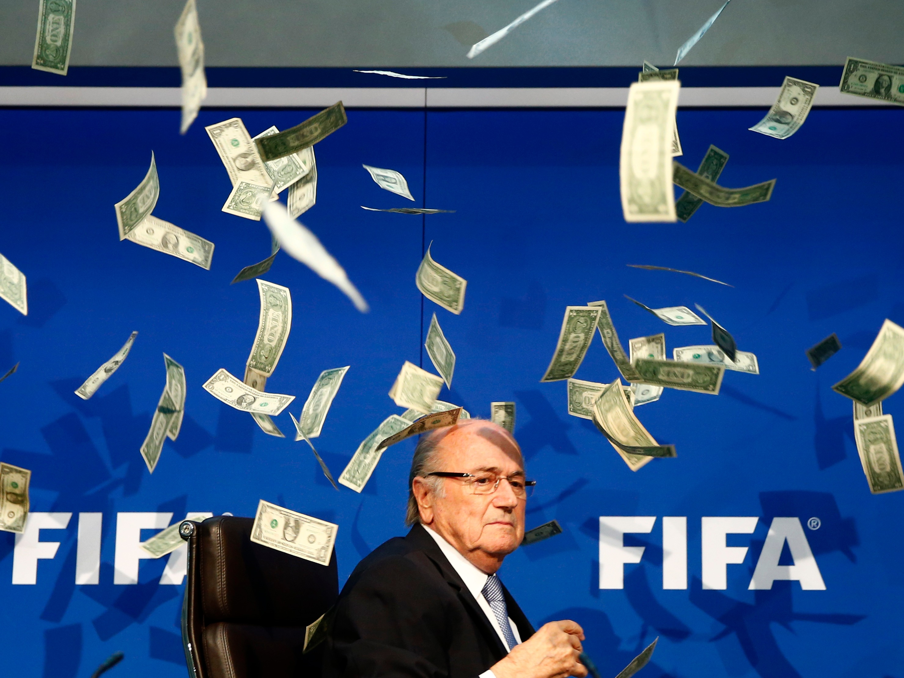 a-protester-threw-a-stack-of-fake-money-at-fifa-president-sepp-blatter-during-a-press-conference